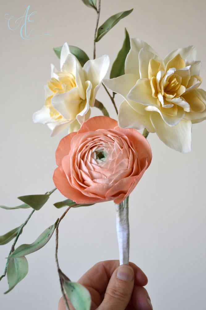 Sugar pale yellow heirloom daffodils peach blush ranunculus and foliage arrangement