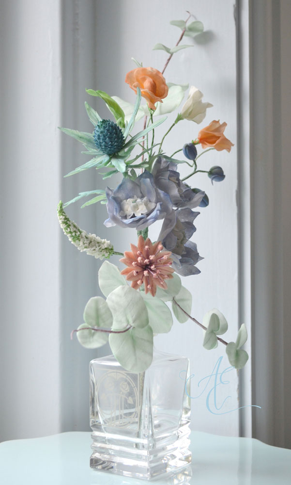 blue and peach sugar arrangement of sweet peas sea holly delphiniums astrantia