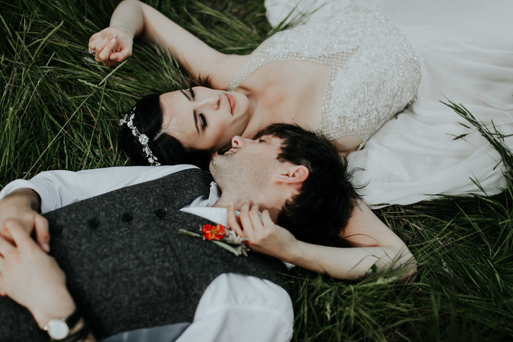 bride and groom laying in field