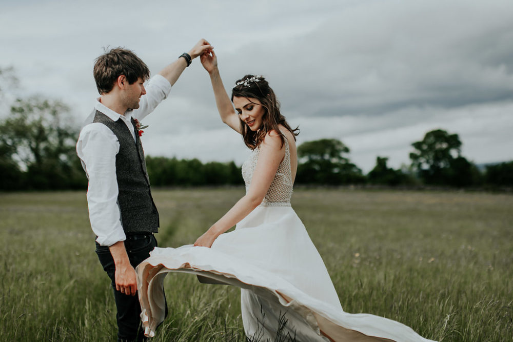 bride and groom twirling in field