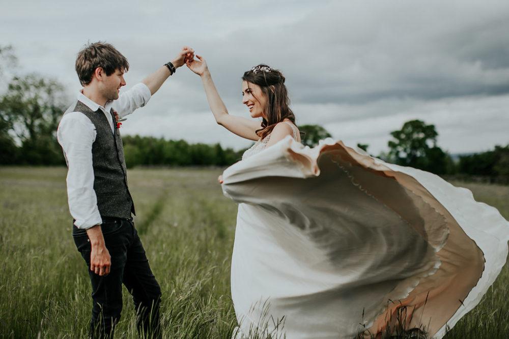 bride and groom dancing in field
