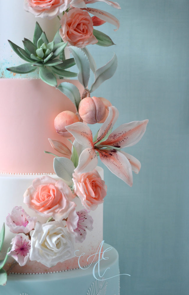 mint peach wedding cake close up sugar lilies rose and peaches