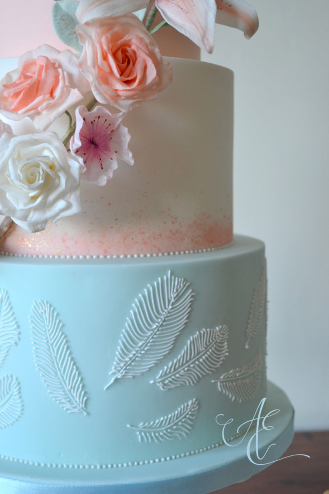 close up wedding cake with hand piped feathers