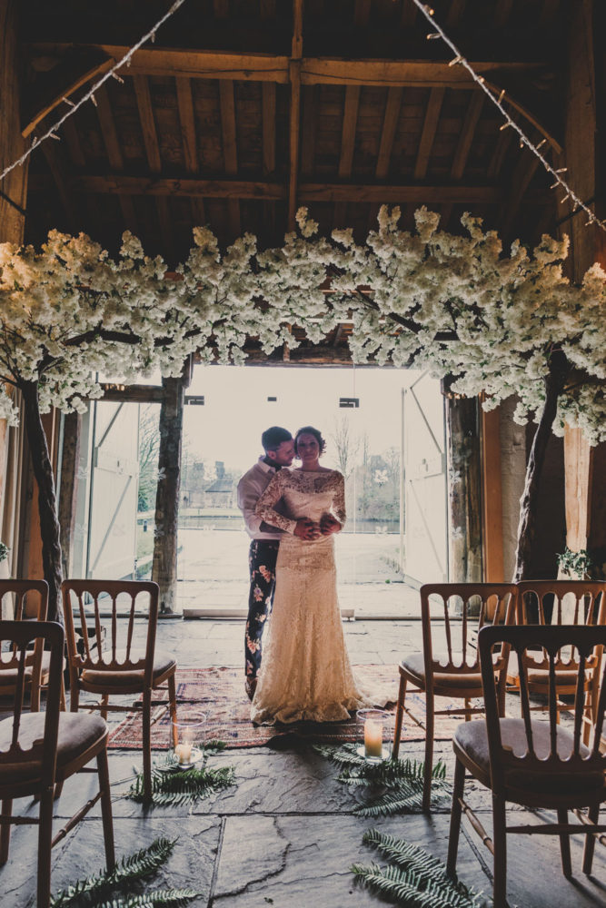 bride and groom embrace beneath blossam canopy barn wedding