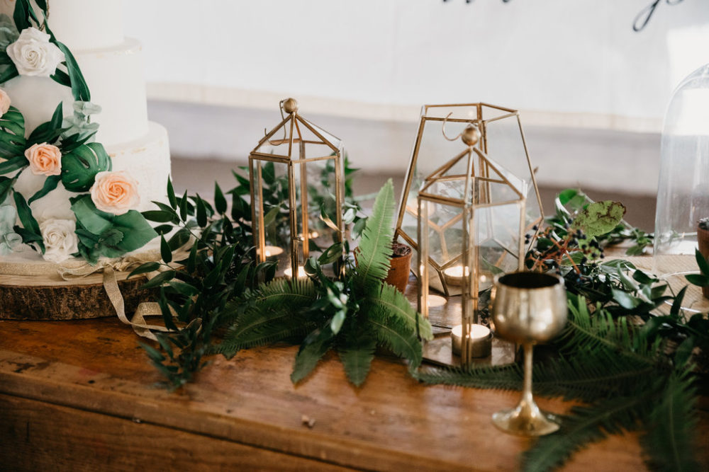 Geometric brass vases and goblet alongside wedding cake