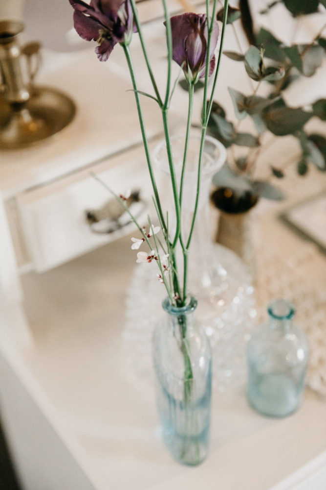 lisianthus stems in glass bottle