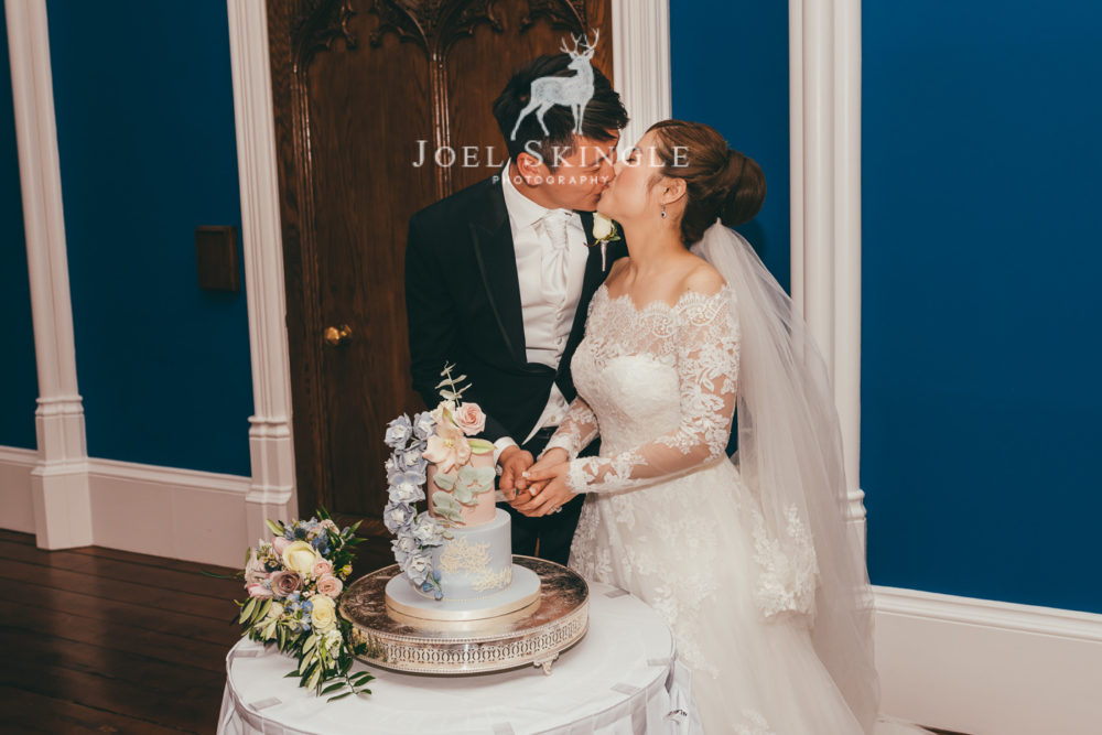 bride and groom kissing whilst cutting their cake