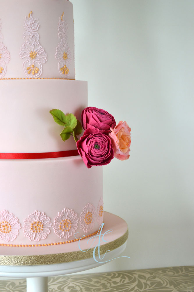 close up pink wedding cake with gilded hand piping