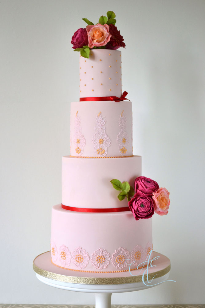 wedding cake with vibrant sugar flowers and gilded piping