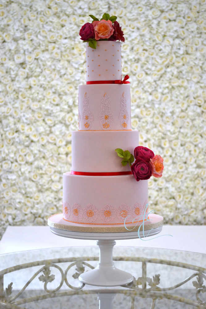 pink wedding cake crowned with vibrant sugar flowers