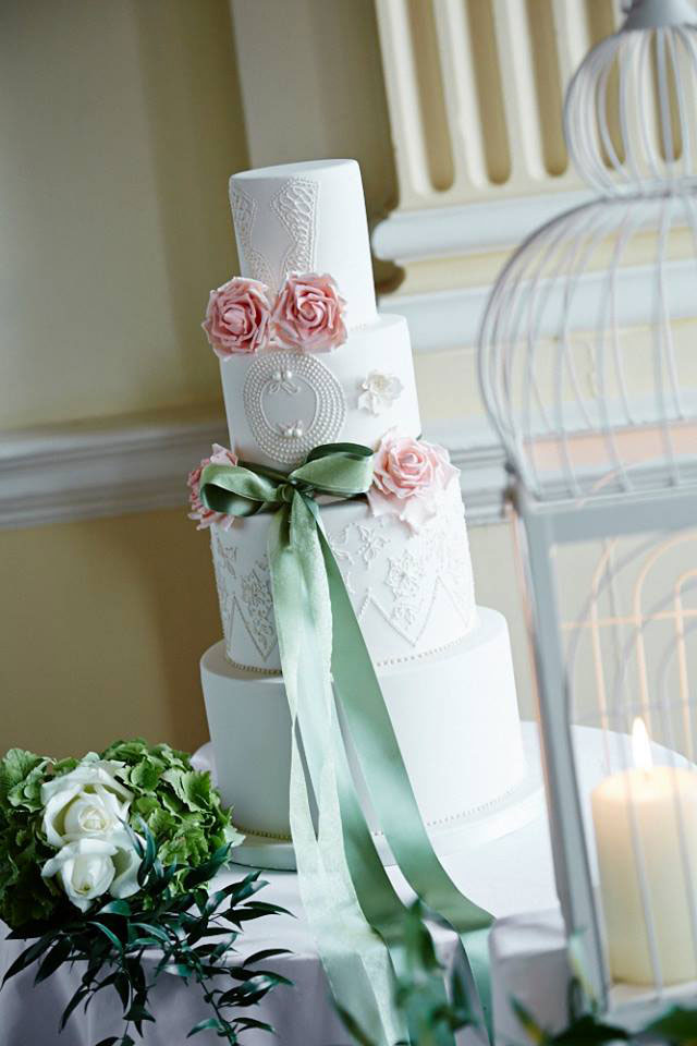 Wedding cake with rose, lace and green ribbon
