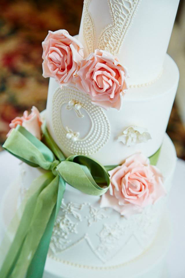 close up peach rose and hand piped wedding cake
