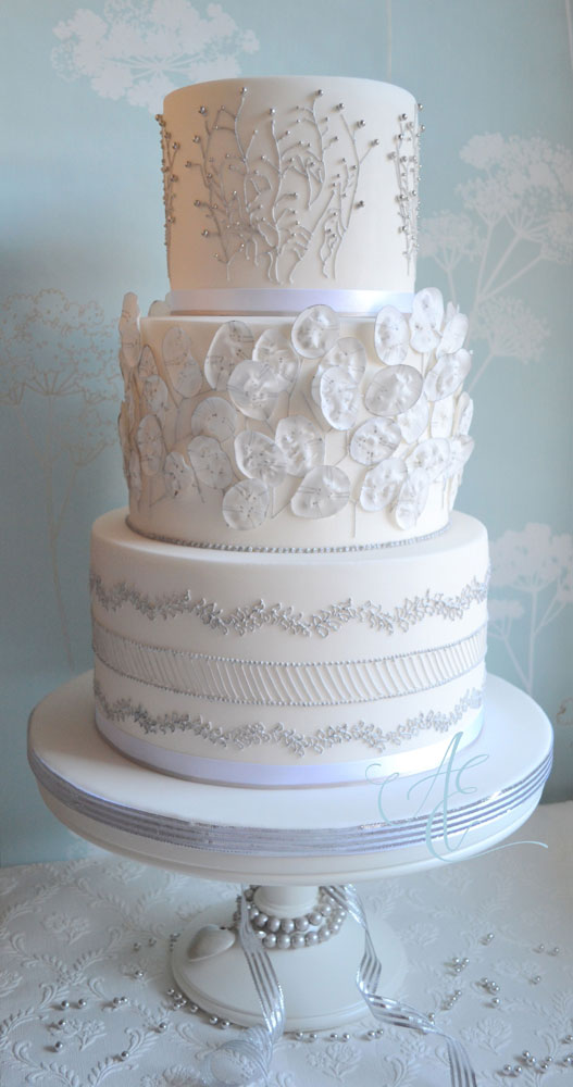 Wedding cake with silver piping and honesty