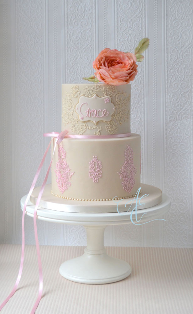 christening cake with hand piped lace and peachy sugar rose