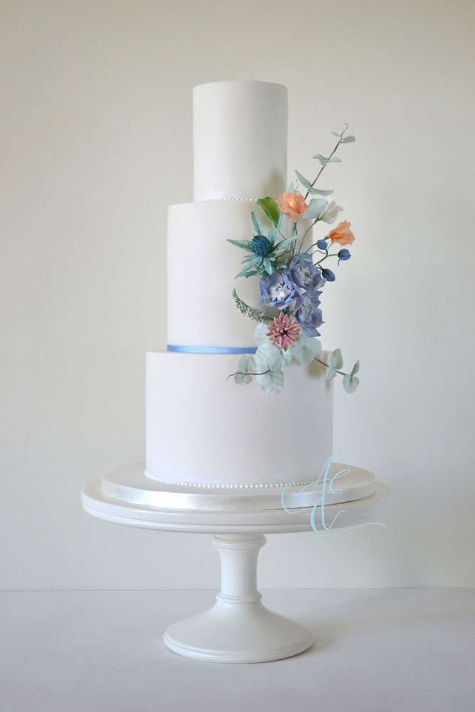 wedding cake with blue pink and peach bouquet of sugar flowers