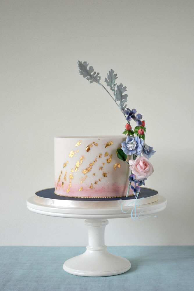 single tier wedding cake with watercolour and gold leaf accents and sugar floral stem