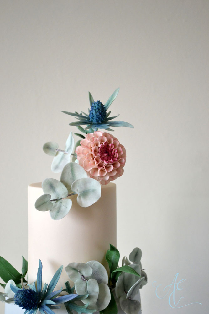 close up sugar pompom dahlia sea holly wedding cake