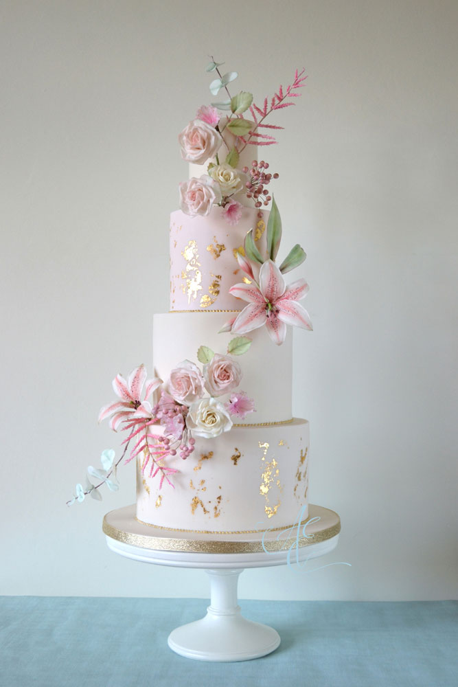 blush ivory and gold wedding cake with a cascade of sugar flowers