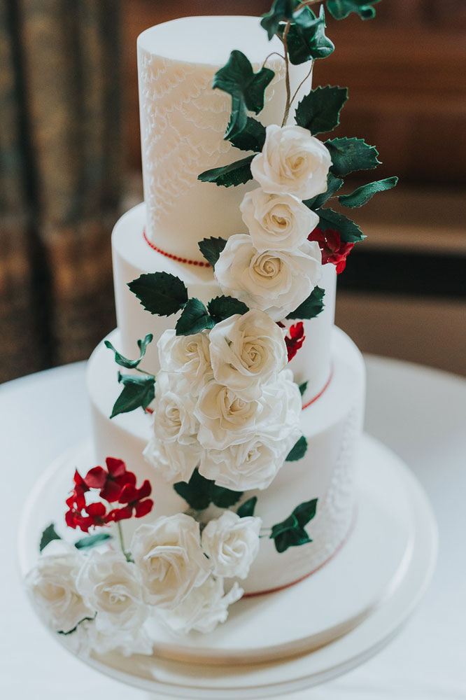 white rose cascade with red blossoms weddding cake