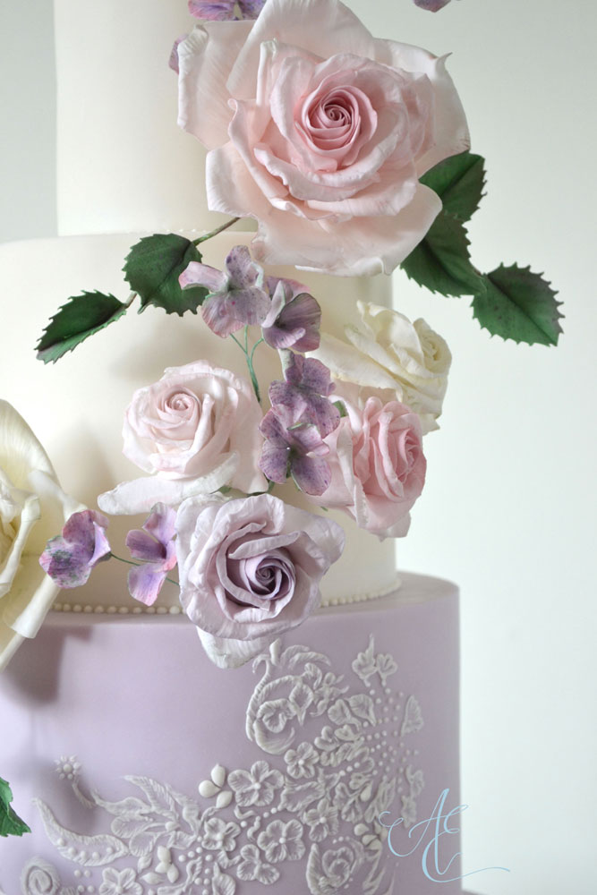 close up pink and lilac sugar roses and hand piped lace