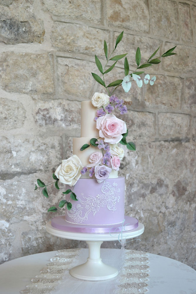 ivory and lilac floral wedding cake at the priests house