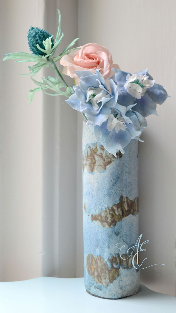 vase of blue sugar delphiniums sea holly and rose