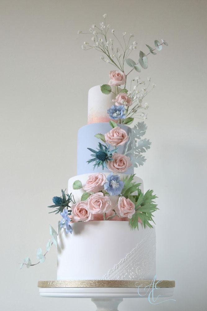 wedding cake with blush and blue sugar flowers tithe barn wedding
